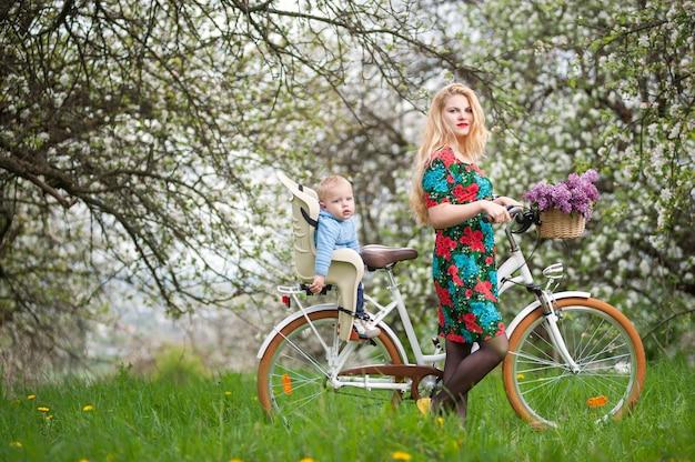 Blonde frau mit stadtfahrrad mit baby im fahrradstuhl