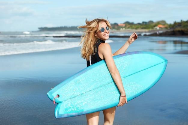 Blonde frau mit surfbrett am strand