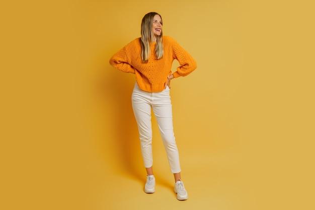 Blonde frau mit überraschungsgesicht in orange stilvollem herbstpullover, der auf gelb aufwirft. volle länge.