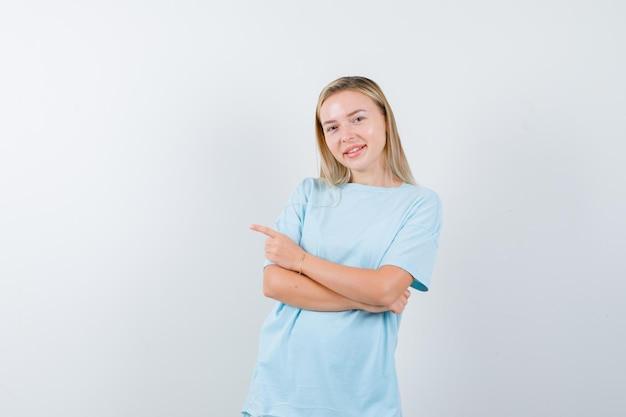 Blonde frau mit verschränkten armen, die mit dem zeigefinger nach links zeigt, im blauen t-shirt