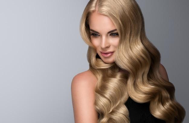 Blonde frau mit voluminösen locken, ausgezeichneten haarwellen. wunderschönes modell mit langem, dichtem, krausem haar und zartem make-up mit rosenlippenstift. friseurkunst, haarpflege und make-up.