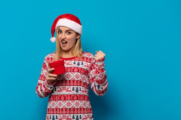Blonde frau mit weihnachtsmütze, die aggressiv mit einem wütenden ausdruck oder mit geballten fäusten schreit, um erfolg zu feiern