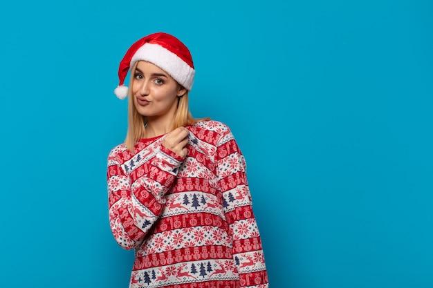 Blonde frau mit weihnachtsmütze, die arrogant, erfolgreich, positiv und stolz aussieht und auf sich selbst zeigt