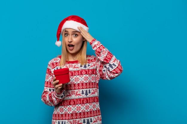 Blonde frau mit weihnachtsmütze, die glücklich, erstaunt und überrascht aussieht, lächelt und erstaunliche und unglaubliche gute nachrichten realisiert
