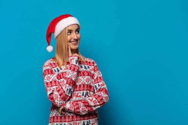 Blonde frau mit weihnachtsmütze, die glücklich lächelt und tagträumen oder zweifel hat