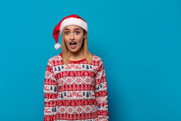 Blonde frau mit weihnachtsmütze, die sehr schockiert oder überrascht aussieht und mit offenem mund starrt und wow sagt