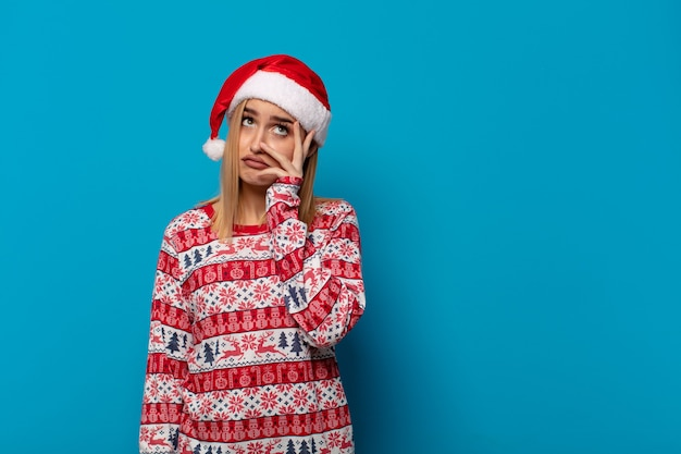 Blonde frau mit weihnachtsmütze, die sich nach einer ermüdenden, langweiligen und mühsamen aufgabe gelangweilt, frustriert und schläfrig fühlt und gesicht mit hand hält