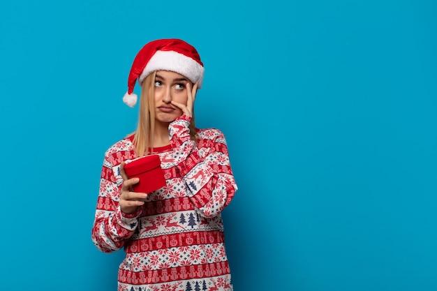 Blonde frau mit weihnachtsmütze, die sich nach einer lästigen, langweiligen und mühsamen aufgabe gelangweilt, frustriert und schläfrig fühlt und gesicht mit hand hält