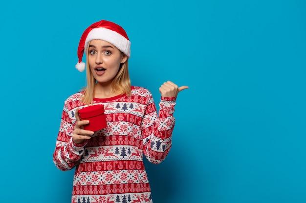 Blonde frau mit weihnachtsmütze, die ungläubig erstaunt aussieht, auf einen gegenstand auf der seite zeigt und wow sagt, unglaublich