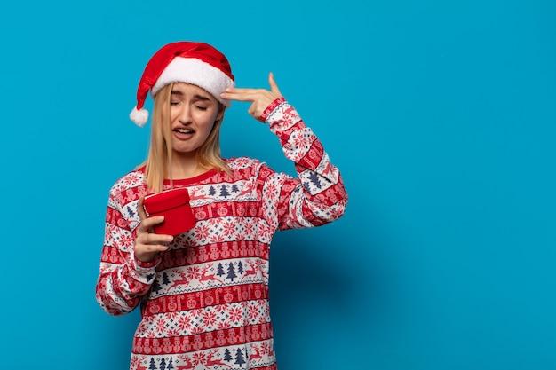 Blonde frau mit weihnachtsmütze, die unglücklich und gestresst aussieht, selbstmordgeste, die waffenzeichen mit hand macht
