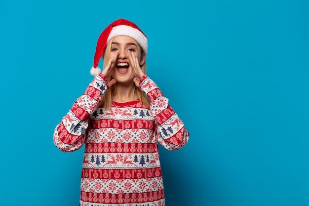 Blonde frau mit weihnachtsmütze fühlt sich glücklich, aufgeregt und positiv, gibt einen großen schrei mit den händen neben dem mund und ruft
