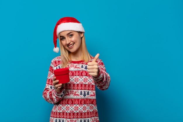 Blonde frau mit weihnachtsmütze fühlt sich stolz, sorglos, selbstbewusst und glücklich und lächelt positiv mit daumen hoch