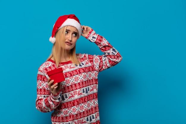 Blonde frau mit weihnachtsmütze fühlt sich verwirrt und verwirrt, kratzt sich am kopf und schaut zur seite