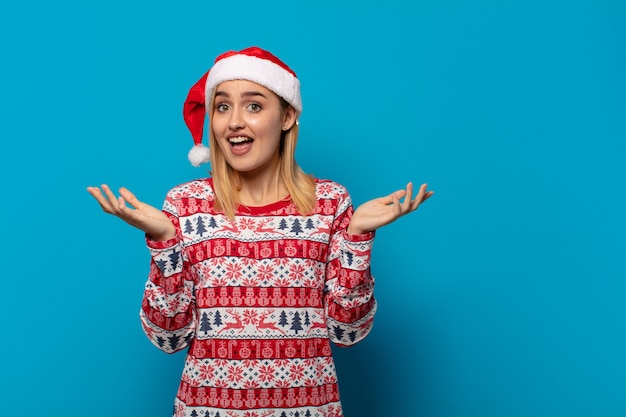 Blonde frau mit weihnachtsmütze, glücklich, aufgeregt, überrascht oder geschockt, lächelnd und erstaunt über etwas unglaubliches