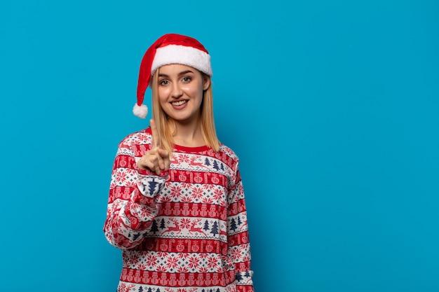 Blonde frau mit weihnachtsmütze lächelnd und freundlich aussehend, zeigt nummer eins oder zuerst mit der hand nach vorne, countdown