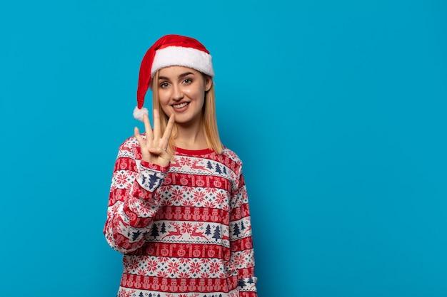 Blonde frau mit weihnachtsmütze lächelnd und freundlich aussehend, zeigt nummer vier oder vierten mit der hand nach vorne, countdown