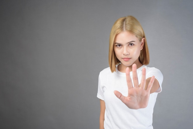 Blonde frau mit weißem t-shirt posiert auf grau