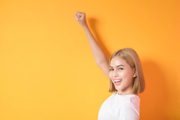 Blonde frau mit weißem t-shirt posiert auf orange