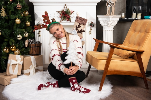 Blonde frau mit weißem weihnachtsbaum, der nahe dem kamin aufwirft.