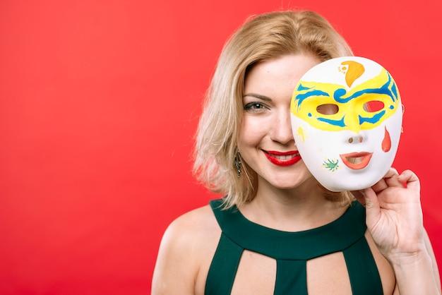 Blonde frau mit weißer karnevalsmaske in der hand