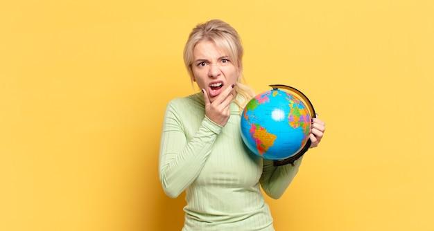 Blonde frau mit weit geöffnetem mund und augen und hand am kinn, die sich unangenehm schockiert fühlt, was sagt oder wow