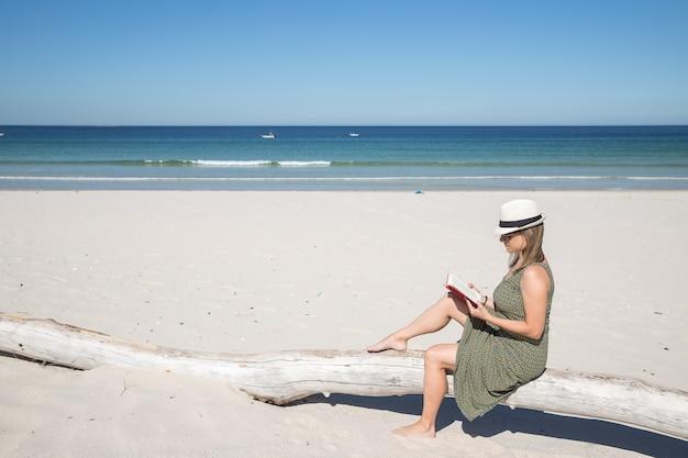 Blonde frau mittleren alters, die auf einem baumstamm im strand sitzt und ein buch liest