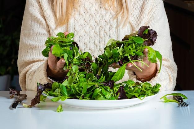 Blonde frau mittleren alters, die salat in der küche isst, gesundes nahrungsmittelkonzept, nahaufnahme