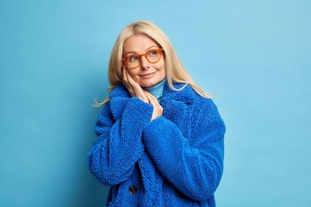 Blonde frau mittleren alters in brillen erinnert sich an etwas angenehmes hält hände in der nähe des gesichts denkt über zukünftige blicke beiseite, lächelt sanft und trägt einen warmen blauen wintermantel.