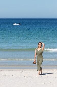 Blonde frau mittleren alters in einem grünen kleid, das barfuß auf dem strand geht