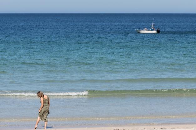 Blonde frau mittleren alters in einem grünen kleid entspannt sich am strand