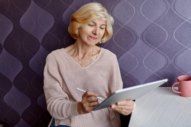 Blonde frau mittleren alters mit tablette