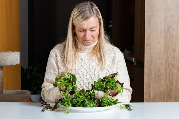 Blonde frau mittleren alters mit unzufriedenem gesichtsausdruck, der salat in der küche, gesundes essen und diätkonzept isst