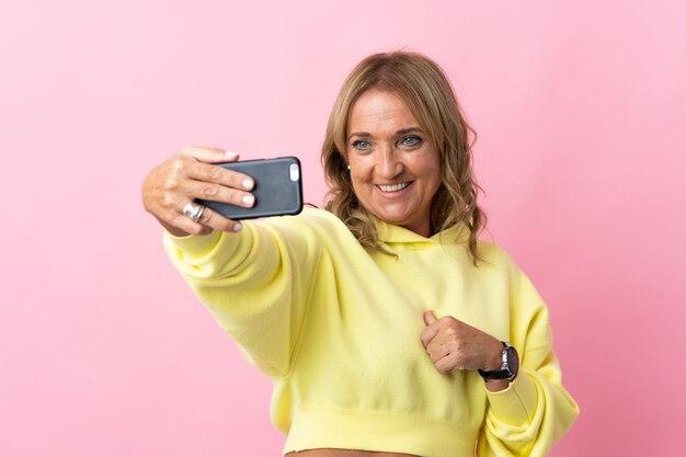Blonde frau mittleren alters über lokalisiertem rosa hintergrund, der ein selfie mit handy macht