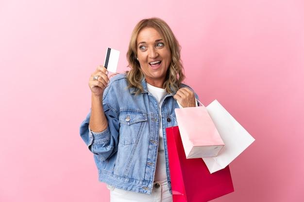 Blonde frau mittleren alters über lokalisiertem rosa hintergrund, der einkaufstaschen und eine kreditkarte hält