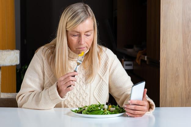 Blonde frau mittleren alters unter verwendung des smartphones beim essen des salats in der küche, lebensstilkonzept