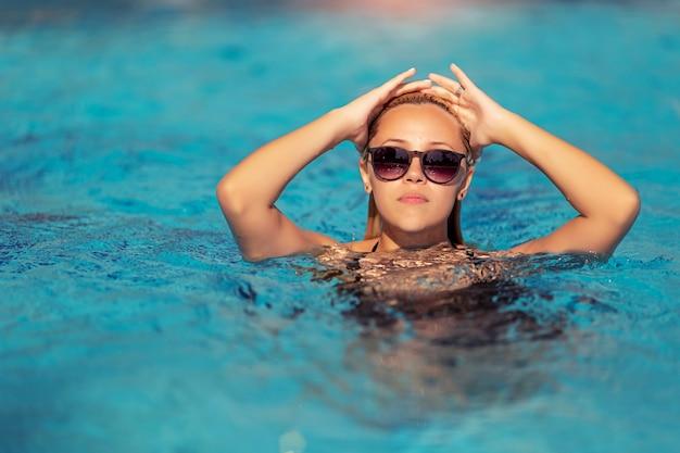 Blonde frau posiert am pool