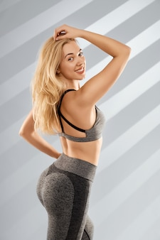 Blonde frau posiert in trendiger grauer sportkleidung