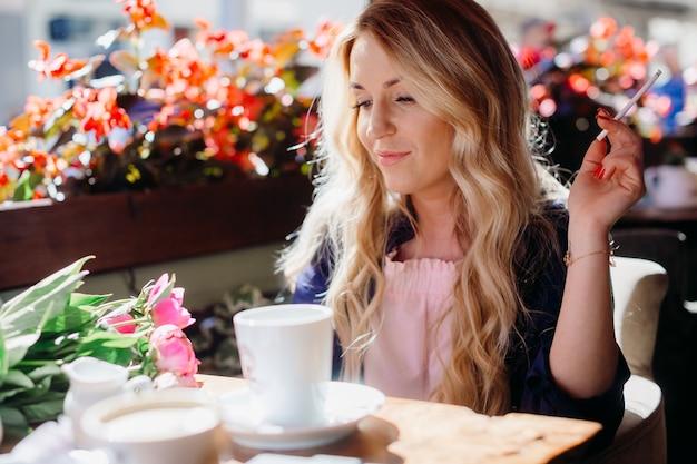 Blonde frau raucht eine zigarre trinkt kaffee im café
