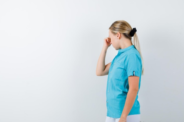 Blonde frau reibt augen und nase in blauer bluse und sieht erschöpft isoliert aus