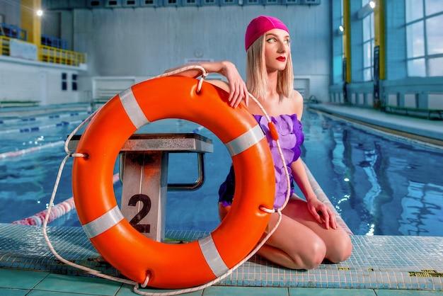 Blonde frau rettungsschwimmer mit make-up in badekappen und badeanzug im schwimmbad mit rettungsring