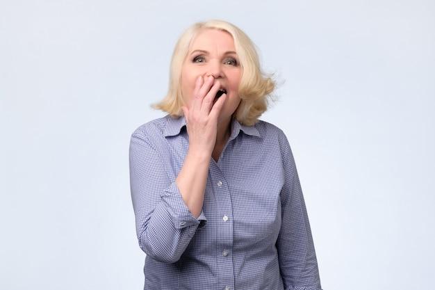Blonde frau schockiert, mund mit hand in überraschung bedeckend