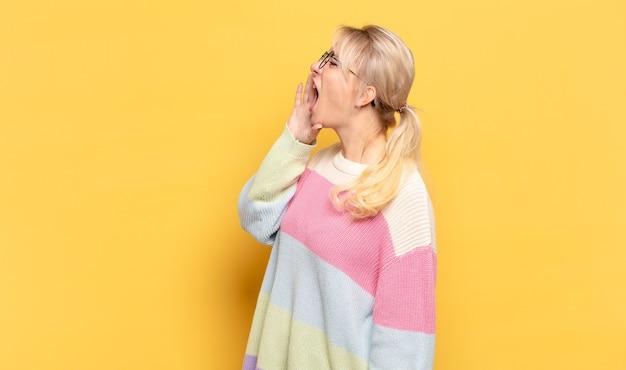 Blonde frau schreit laut und wütend, um platz auf der seite zu kopieren, mit der hand neben dem mund