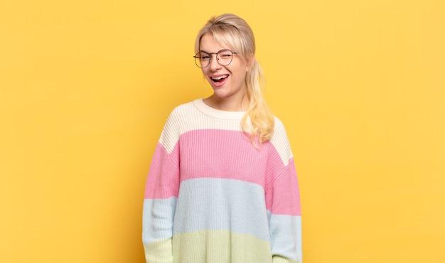Blonde frau sieht glücklich und freundlich aus, lächelt und zwinkert ihnen mit einer positiven einstellung zu