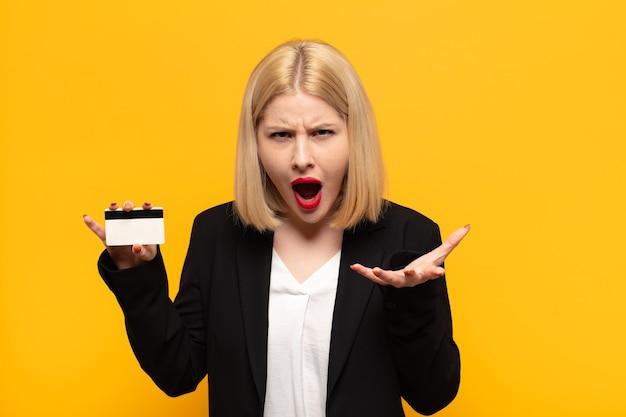 Blonde frau sieht wütend, verärgert und frustriert aus und schreit wtf
