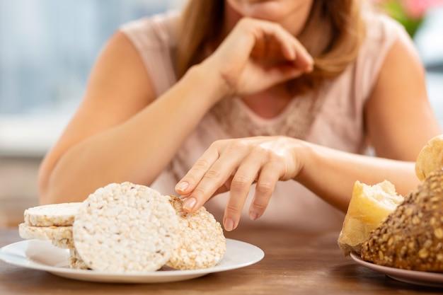 Blonde frau sitzt am tisch und isst chips, kein brot wegen allergie