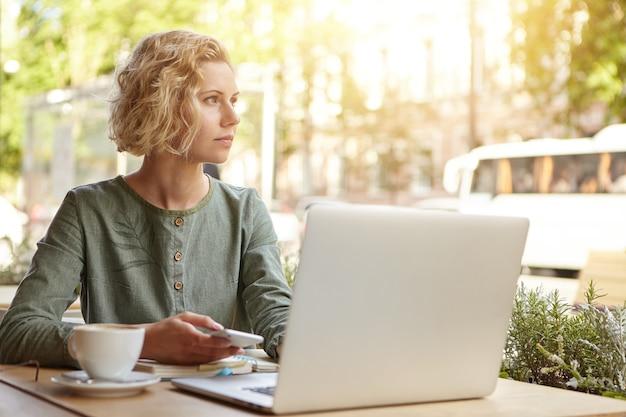 Blonde frau sitzt mit laptop im café