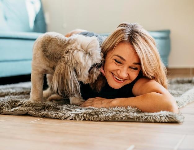 Blonde frau streichelt niedlichen kleinen hund