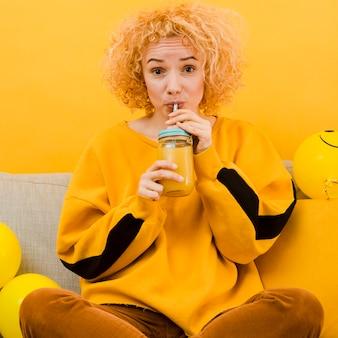 Blonde frau trinkt einen smoothie