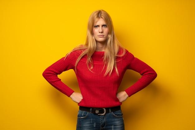 Blonde frau über gelber wand überrascht und eine mitteilung sendend