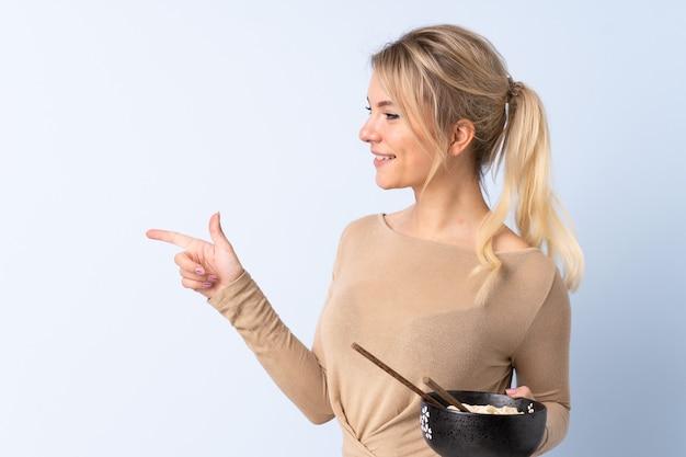Blonde frau über isoliertem blauem hintergrund, der zur seite zeigt, um ein produkt zu präsentieren, während eine schüssel nudeln mit stäbchen hält